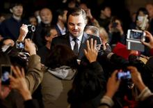 "Oscar-winning actor Leonardo DiCaprio (C) signs autographs for fans during the Japan premiere of his movie ""The Revenant"" in Tokyo, Japan, March 23, 2016. REUTERS/Toru Hanai"