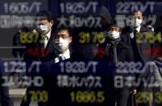 Peatones se reflejan en un tablero electrónico que muestra los índices de mercado de varios países, afuera de una correduría en Tokio, Japón, 26 de febrero de 2016. El dólar avanzaba por quinta sesión consecutiva el jueves, aumentando la presión sobre las materias primas y las bolsas de Asia después de que otro funcionario de la Reserva Federal de Estados Unidos se refirió a la posibilidad de que haya más de un aumento en las tasas de interés este año. REUTERS/Yuya Shino