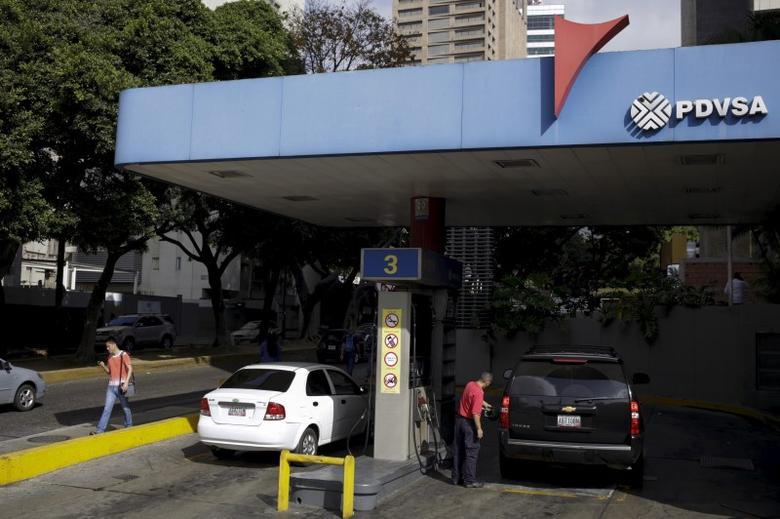 A worker pumps gas into a vehicle at a gas station, which belongs to Venezuela's state oil company PDVSA, in Caracas, February 12, 2016. REUTERS/Marco Bello