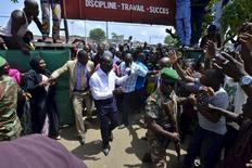 Benin Presidential candidate Patrice Talon (C, in white) arrives at a polling station during presidential elections in Cotonou, Benin, March 20, 2016. REUTERS/Charles Placide Tossou