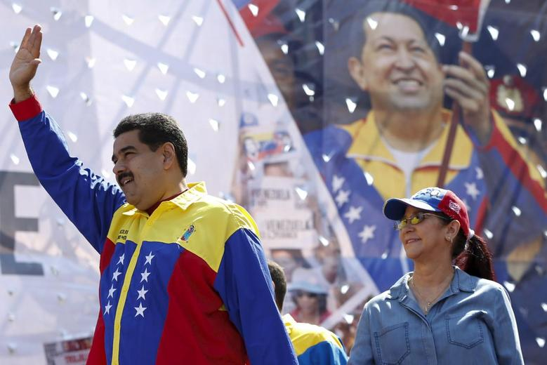 Venezuela's President Nicolas Maduro (L) waves next to his wife and deputy of Venezuela's United Socialist Party (PSUV) Cilia Flores and in front of a picture of Venezuela's late President Hugo Chavez, during a rally in Caracas March 12, 2016. REUTERS/Carlos Garcia Rawlins