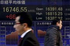 Personas caminan junto a un tablero electrónico que muestra el índice Nikkei, afuera de una correduría en Tokio, Japón, 2 de marzo de 2016. Las acciones japonesas subieron el lunes a un máximo de dos semanas gracias a un yen más débil, mientras que los papeles de Sharp saltaron por las expectativas de que finalmente se concrete su venta a una empresa taiwanesa. REUTERS/Thomas Peter