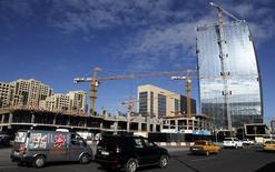 Машины проезжают мимо строящихся зданий в столице Азербайджана Баку. 3 ноября 2010 года. Совет директоров Всемирного банка предоставил Азербайджану кредит в размере $140 миллионов на завершение проекта расширения автодороги, сообщает бакинский офис Всемирного банка. REUTERS/Osman Karimov