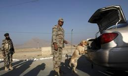 Солдат с собакой проверяют машину на пропуском пункте на автотрассе близ Кветты. 30 ноября 2015 года. Власти Пакистана задержали более 5.000 подозреваемых в связи со взрывом боевика-смертника в Лахоре в воскресенье, в результате которого погибло более 70 человек, сообщил министр провинции во вторник. REUTERS/Naseer Ahmed