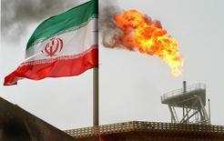 Флаг Ирана на нефтедобывающей платформе в Персидском заливе. 25 июля 2005 года. Входящий в состав ОПЕК Иран должен посетить встречу производителей нефти в Дохе в апреле, но это не означает, что он примет участие в переговорах о заморозке добычи, сказал Рейтер источник, знакомый с позицией Ирана, во вторник. REUTERS/Raheb Homavandi
