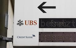 Логотипы UBS и Credit Suisse на вывеске в Цюрихе. 13 февраля 2013 года. Два работающих в России швейцарских инвестбанка - UBS и Credit Suisse - откликнулись на предложение российского правительства подавать заявки на участие в трех первых в этом этапе приватизации сделках, сказали Рейтер банковские источники. REUTERS/Michael Buholzer