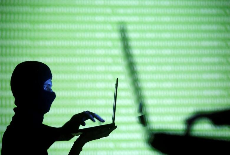 People wearing balaclavas are silhouetted as they pose with a laptops in front of a screen projected with the word 'cyber' and binary code, in this picture illustration taken in Zenica October 29, 2014.  REUTERS/Dado Ruvic