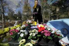 Pet owner Ma Ying cleans the glass covering her dog Liu Dazhuang's tomb, with bathtub, dolls and decoration flowers placed inside, ahead of the Qingming Festival at Baifu pet cemetery on the outskirts of Beijing, China March 27, 2016.  REUTERS/Jason Lee