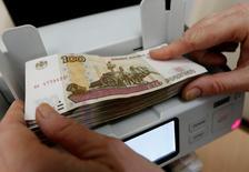 Кассир пересчитывает 100-рублевые банкноты. Рубль растет с самого начала биржевой сессии четверга, что может быть связано с локальным позиционированием и денежными потоками последнего календарного дня первого квартала, с текущей слабостью американского доллара США на мировых рынках, а также и  за счет разворота в плюс с полумесячных минимумов нефтяных котировок. REUTERS/Ilya Naymushin