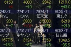 Personas se reflejan en una pantalla que muestra índices de mercado, afuera de una correduría en Tokio, Japón. 10 de febrero de 2016. Las bolsas de Asia subían el jueves a máximos en cuatro meses, en momentos en que unas menores expectativas de alzas en el corto plazo a las tasas de interés en Estados Unidos seguían avivando el apetito de los inversores por activos de mayor riesgo. REUTERS/Thomas Peter