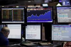 Трейдеры работают на фондовой бирже Нью-Йорка. Американские фондовые индексы в понедельник слабо снижаются на фоне падения цен на нефть, которое ударило по акциям сырьевого сектора, нивелировав влияние роста бумаг сектора здравоохранения. REUTERS/Brendan McDermid