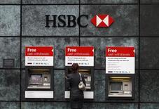 Женщина у банкомата HSBC в Лондоне. 28 февраля 2011 года. Credit Suisse и HSBC, одни из крупнейших банков мира, во вторник опровергли предположения о том, что они активно использовали офшорные структуры, чтобы помогать своим клиентам уходить от налогов. REUTERS/Andrew Winning