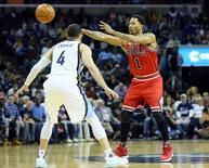 Chicago Bulls guard Derrick Rose (1) passes as Memphis Grizzlies guard Jordan Farmar defends at FedExForum. Memphis defeated Chicago 108-92. Mandatory Credit: Nelson Chenault-USA TODAY Sports