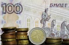 Евро на фоне 100-рублевой банкноты. Рубль пытается расти в начале торгов среды на фоне восстановления нефти в надежде на заморозку добычи и после данных о падении её запасов в США, но сдерживающим динамику фактором могут выступать ожидания публикации протоколов последнего заседания ФРС США в 21.00 МСК. REUTERS/Dado Ruvic