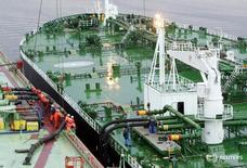 Рабочие готовят танкер к заправке у плавучего нефтяного терминала Белокаменка у Мурманска 19 июня 2006 года. Россия может увеличить экспорт нефти на западном направлении в 2016 году через порты, сказал в пятницу министр энергетики Александр Новак. Sergei Karpukhin / Reuters