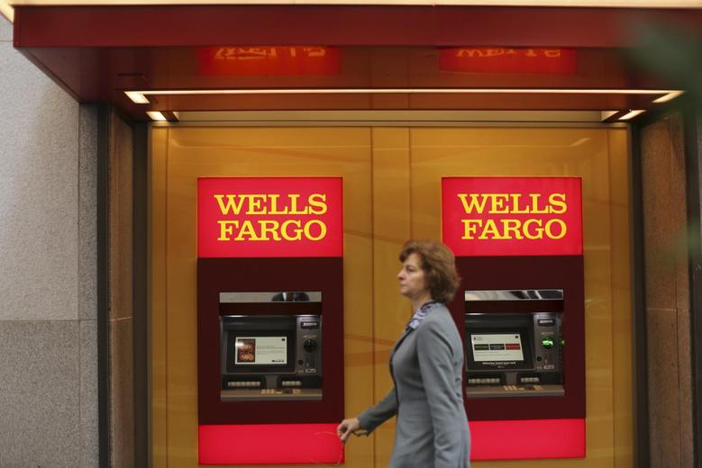 A woman walks past teller machines at a Wells Fargo bank in San Francisco, California in this October 10, 2013 file photo. REUTERS/Robert Galbraith
