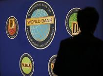 La silueta de un hombre delante del logo del Banco Mundial, durante una reunión del Banco Mundial con el FMI, en Tokio. 10 de octubre de 2012. El Banco Mundial dijo el lunes que espera que su tasa de préstamo fuera del mercado llegue a los 43.000 millones de dólares en el año fiscal actual, ante los vientos de cara que enfrentan los países en desarrollo, elevando su total para los cuatro últimos años a más de 150.000 millones de dólares. REUTERS/Kim Kyung-Hoon