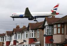 Un avión pasa encima de unas casas antes de aterrizar en el aeropuerto de Heathrow, cerca de Londres, Inglaterra. 11 de diciembre de 2015. La inflación británica registró un máximo en 15 meses en marzo debido a que unos feriados por Semana Santa antes de lo usual elevaron las tarifas aéreas, según datos divulgados el miércoles, enviando una señal de tranquilidad al Banco de Inglaterra (BoE) sobre que el alza de los precios en niveles cercanos a cero está llegando a su fin. REUTERS/Neil Hall