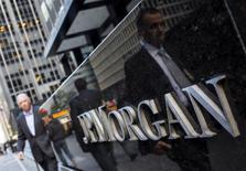 Los reguladores de Estados Unidos se preparan para informar a algunos de los mayores bancos del país, incluido JPMorgan Chase & Co, que han hallado errores en sus planes para enfrentar potenciales crisis, informó el martes el diario Wall Street Journal, citando a fuentes con conocimiento del tema. Imagen de archivo en la que se ve a gente pasando junto al edificio de JP Morgan & Chase Co en Nueva York, el 24 de octubre de 2013. REUTERS/Eric Thayer