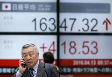 Un hombre camina frente a un tablero electrónico que muestra el índice Nikkei de Japón, afuera de una correduría en Tokio. 13 de abril de 2016. Las bolsas de Asia operaban el miércoles cerca de sus máximos en el 2016 luego de que unos datos comerciales chinos optimistas aumentaron la esperanza de que el gigante asiático se estaría estabilizando, lo que apoyaba el apetito por el riesgo. REUTERS/Toru Hanai