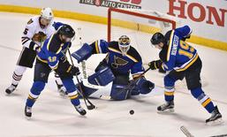Apr 13, 2016; St. Louis, MO, USA; St. Louis Blues center David Backes (42) and Chicago Blackhawks center Jonathan Toews (19) fight to clear the puck against the Chicago Blackhawks during the third period in game one of the first round of the 2016 Stanley Cup Playoffs at Scottrade Center. Jasen Vinlove-USA TODAY Sports