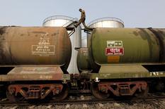 Рабочий идет по вагону-цистерне на нефтяном терминале недалеко от Калькутты.  Нефть торгуется выше $44 за баррель в четверг, после того как Международное энергетическое агентство (МЭА) ухудшило прогноз роста спроса, но сообщило, что спад добычи чёрного золота в США ускоряется, а также после данных о занятости. REUTERS/Rupak De Chowdhuri/Files