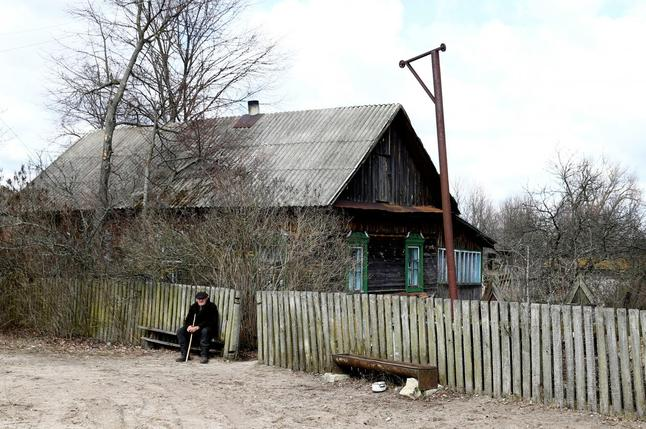 Ivan Shamyanok, 90, sits in front of his house in the village of Tulgovichi, near the exclusion zone around the Chernobyl nuclear reactor, Belarus April 2, 2016.
