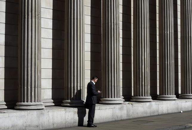 A City worker views his phone outside of the Bank of England in the City of London, Britain, March 29, 2016. REUTERS/Toby Melville