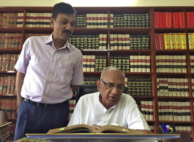 Sita Ram Joshi, a lawyer, reads a book as his son Rahul Joshi (L), also a lawyer, stands next to him while they pose for a picture inside their office in Jaipur, April 9, 2016. REUTERS/Aditya Kalra