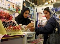 An Iranian woman tests the colours of make-up at an upscale shop in north Tehran in this November 8, 2003 file photo. REUTERS/Morteza Nikoubazl/Files