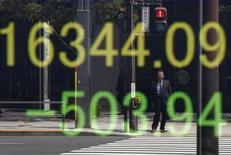 Un hombre se refleja en una pantalla electrónica que muestra el índice Nikkei en el exterior de una casa de valores en Tokio, Japón, 18 de abril de 2016. Las acciones japonesas cayeron el lunes después de que un yen más fuerte dañara las perspectivas de ganancias de las empresas, mientras que el apetito de riesgo se veía afectado por los terremotos en la isla sureña de Kyushu. REUTERS/Toru Hanai
