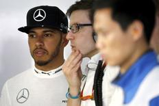 Formula One - Chinese F1 Grand Prix - Shanghai, China - 16/4/16 - Mercedes Formula One driver Lewis Hamilton of Britain stands next to his team members in the garage during the qualifying session. REUTERS/Pool