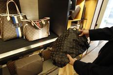 A fake LVMH handbag (R) purchased and shipped from a China -ased online website is pictured next to products on display at a Louis Vuitton store in Chevy Chase, Maryland, October 5, 2010.  REUTERS/Hyungwon Kang