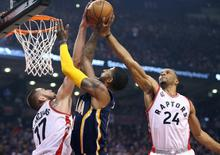 Apr 18, 2016; Toronto, Ontario, CAN; Indiana Pacers forward Paul George (13) has a shot blocked by Toronto Raptors center Jonas Valanciunas (17) and guard Norman Powell (24) in game two of the first round of the 2016 NBA Playoffs at Air Canada Centre. The Raptors beat the Pacers 98-87. Tom Szczerbowski-USA TODAY Sports