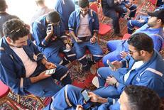 Miles de trabajadores del sector del petróleo y gas de Kuwait finalizaron una huelga de tres días por motivos salariales que redujo la producción del país de la OPEP, dijo el martes en su cuenta de Twitter el periódico local Al Jarida, que citó a un sindicato. En la imagen trabajadores del petróleo de Kuwait sentados con sus móviles durante el primer día de huelga en Ahmadi, Kuwait, el 17 de abril de 2016. REUTERS/Stephanie McGehee