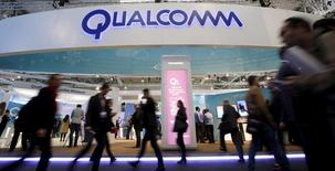 People walk past Qualcomm's stand during the Mobile World Congress in Barcelona, Spain in this February 24, 2016, file photo. REUTERS/Albert Gea/Files