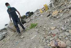 Unas personas buscan objetos para reciclar en Pedernales tras el sismo que afectó la costa del pacífico ecuatoriano, abr 21, 2016. Las aseguradoras enfrentan pedidos de pagos por daños de hasta 850 millones de dólares debido al sismo de magnitud 7,8 que sacudió a Ecuador el 16 de abril, dijo el jueves la firma AIR Worldwide, que hace estimaciones de los costos de los desastres naturales.  REUTERS/Guillermo Granja