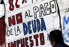 """Argentina dejó atrás el viernes una suspensión de pagos de 14 años con la cancelación de más de 9.000 millones de dólares de deuda a fondos conocidos como """"holdouts"""", tras un extenso conflicto judicial que impedía al país acceder a los mercados voluntarios de crédito. En la imagen, un hombre mira un grafiti que dice """"No al pago de la deuda"""" en Buenos Aires, Argentina, el 22 de abril de 2016.  REUTERS/Marcos Brindicci"""