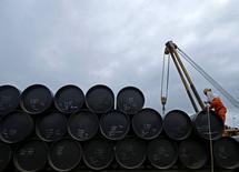 Un trabajador prepara barriles de petróleo para transportarlos, en Johor. 4 de febrero de 2015. Un repunte de los precios del petróleo desde mínimos de 12 años está en peligro de detenerse en la medida en que las actividades de refinación, el principal motor de crecimiento de la demanda global de los últimos años, comienza a vacilar ante señales de un exceso de gasolina. REUTERS/Edgar Su/Files