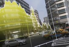 Офисное здание в Токио отражается в электронном табло, показывающем график обменного курса иены. Иена выросла к основным валютам во вторник, отодвинувшись от минимумов трех недель к доллару и евро, однако все еще находится под давлением опасений в преддверии заседания Банка Японии на этой неделе, которое последует за встречей Федрезерва США.  REUTERS/Toru Hanai