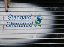 Una mujer baja por las escaleras de la sede de Standard Chartered, en Hong Kong. 13 de octubre de 2010. Standard Chartered dijo que sus ganancias en los primeros tres meses de este año cayeron en torno a un 59 por ciento frente al mismo período del 2015, luego de que el aumento en los cargos por morosidad y la debilidad del entorno global de negocios se hicieron sentir. REUTERS/Bobby Yip/File Photo