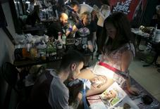 Tattoo artists work on clients during the second International Tattoo Festival in Sochi, Russia, April 23, 2016. REUTERS/Kazbek Basayev