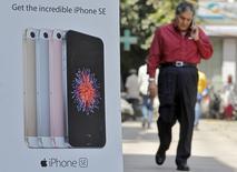 Мужчина говорит по телефону, проходя мимо рекламы смартфонов Apple в Дели 25 апреля 2016 года. Apple Inc во вторник сообщила о первом в истории падении продаж iPhone и о первом снижении выручки за 13 лет, поскольку компания, которая считается первопроходцем на рынке смартфонов, испытывает трудности на всё более насыщенном рынке. REUTERS/Anindito Mukherjee