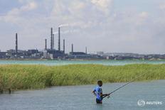 Человек рыбачит у завода Казахмыса в городе Балхаш, Казахстан 15 июня 2012 года. Экономика Казахстана, зависящая от мировых цен на нефть и металлы, по предварительным данным, снизилась в первом квартале 2016 года на 0,2 процента по сравнению с ростом на 2,2 процента в январе-марте прошлого года, сказал журналистам министр экономики Ерболат Досаев. REUTERS/Robin Paxton