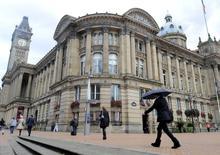 La economía británica se desaceleró a principios de año, afectada por la debilidad de la economía global y la incertidumbre previa al referéndum de este año sobre la pertenencia de Reino Unido a la Unión Europea, al depender únicamente del sector de servicios para generar crecimiento. En la imagen, unos transeúntes pasan por el ayuntamiento en Birmingham en el centro de Inglaterra el 6 de octubre de 2010. REUTERS/Toby Melville/File Photo