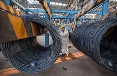 Un trabajador inspecciona bobinas de acero en una planta en Lianyungang, provincia de Jiangsu, China. 11 de octubre de 2014. Una importante bolsa de materias primas de China tomó el miércoles nuevas medidas para calmar la volatilidad de los mercados, al elevar sus tarifas por operaciones y extender los límites sobre las oscilaciones de los precios, lo que podría hacer más ordenados los contratos a futuro. REUTERS/China Daily