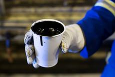 A worker holds a cup of heavy oil before it is shipped to the market at the Cenovus Energy Christina Lake Steam-Assisted Gravity Drainage (SAGD) project 120 km (74 miles) south of Fort McMurray, Alberta, August 15, 2013. REUTERS/Todd Korol