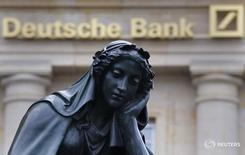 Статуя на фоне логотипа Deutsche Bank во Франкфурте-на-Майне 26 января 2016 года. Немецкий Deutsche Bank сообщил о неожиданных результатах квартальной прибыли благодаря снижению судебных издержек. REUTERS/Kai Pfaffenbach/File Photo