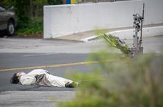 A man, claiming to have a bomb, lays in the street outside of the Fox45 television station, which was evacuated due to a bomb threat, in Baltimore, Maryland, U.S. April 28, 2016.  REUTERS/Bryan Woolston