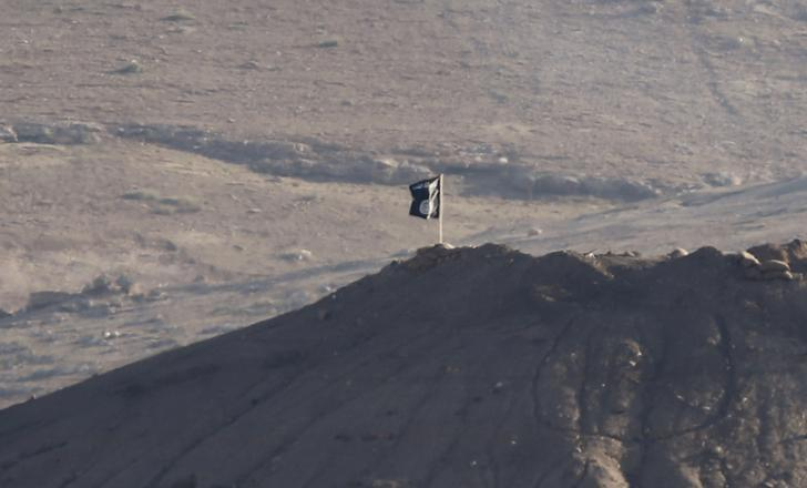 A black flag belonging to the Islamic State is seen near the Syrian town of Kobani, as pictured from the Turkish-Syrian border near the southeastern town of Suruc in Sanliurfa province, in this file photo dated October 6, 2014. IREUTERS/Umit Bektas